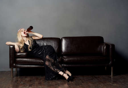 Beautiful blonde woman on the couch with a bottle of beer and in a black dress