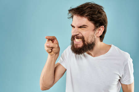 Man with disgruntled facial expression gesturing with hands studio lifestyle blue background Imagens