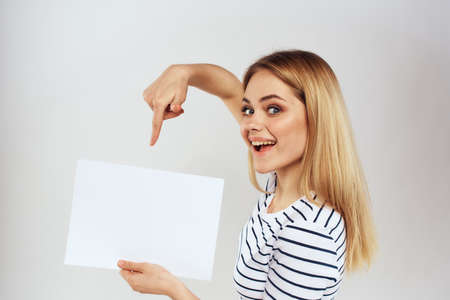 woman holding a sheet of paper in her hands lifestyle striped t-shirt cropped view Copy Space