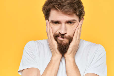 Man in white t-shirt emotions studio gestures with hands displeased facial expression yellow background 版權商用圖片