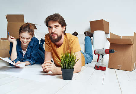 Moving to an apartment a man and a woman lie on the floor and a flower in a pot Imagens