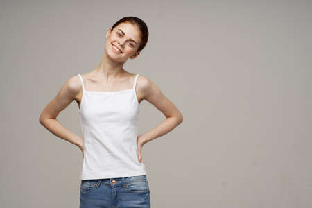 pretty red-haired woman in white t-shirt and jeans smile studio lifestyle
