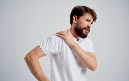 man has shoulder pain and white t-shirt dislocation health problems Stok Fotoğraf