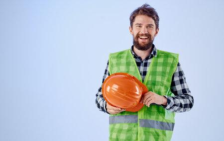 Builder with orange hard hat in hand and reflective vest blue background Copy Space Banco de Imagens