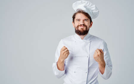 Professional chefs in uniforms are gesturing with their hands on a light background
