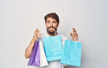 Bearded man in white t-shirt with packages in hands shopping holiday isolated sign