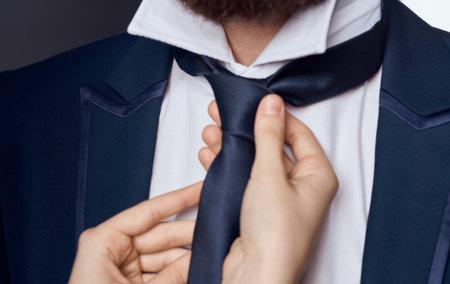 Womens hands tie around the neck of men classic suit model beard