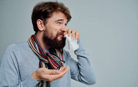 a man with a cold wipes his nose with a handkerchief health problems pills medicine
