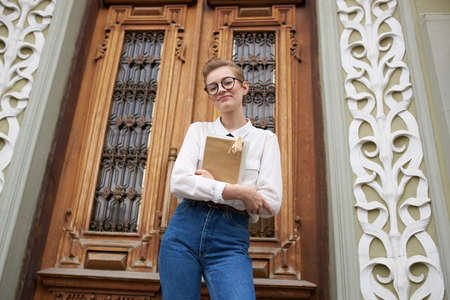 female student in glasses and jeans near the door on the street Institute of Education Faculty Stock fotó