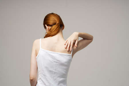 woman white t-shirt touching her shoulders with hands cropped view close-up