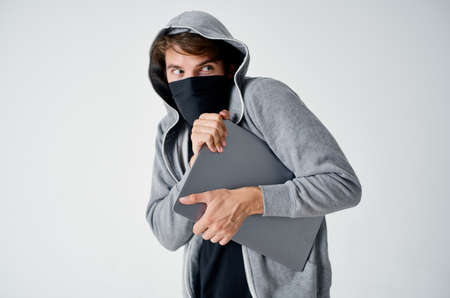 man with a hood on his head mask laptop theft illegal entry crime Standard-Bild