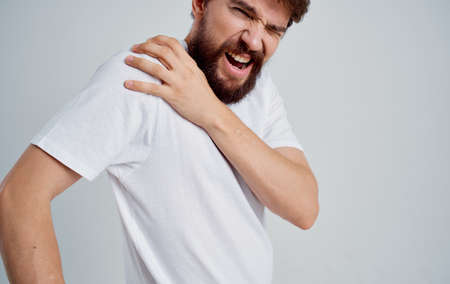 man touching shoulder with hand dislocation discomfort white t-shirt Stok Fotoğraf