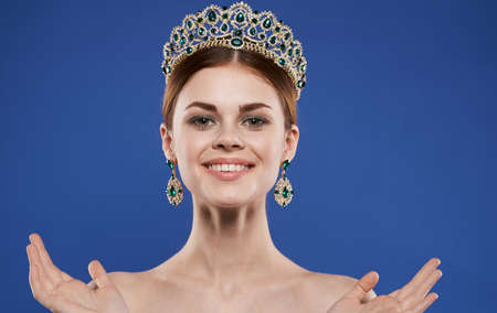 Charming lady with a crown on her head and earrings makeup blue background