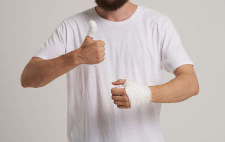 man wearing white t-shirt patient bandaged hand health problems emergency room