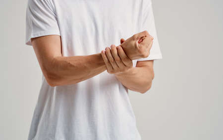 a man in a white t-shirt touches his wrists on a light background