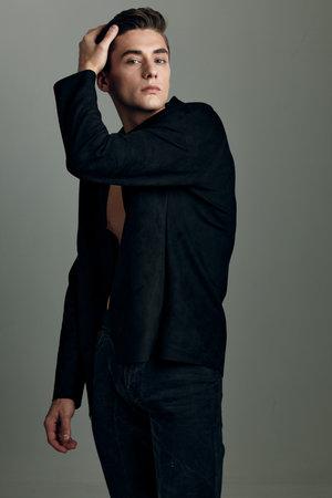 Handsome man black jacket hand on head trendy hairstyle modern style fashion