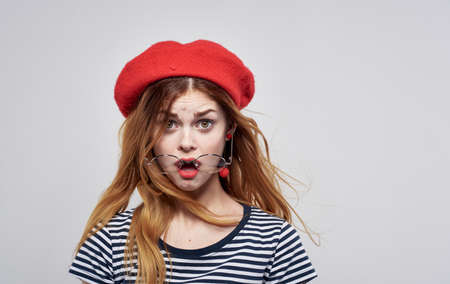 Frenchwoman in a red hat and in a striped T-shirt glasses model portrait close-up Foto de archivo