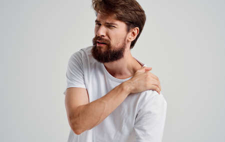 bearded man touching shoulder with hand pain dislocation medical intervention Stok Fotoğraf