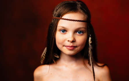 Cute little girl with feathers in her hair Apache hairstyle close-up