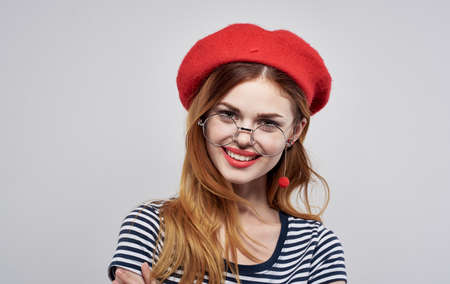 Beautiful woman in red hat Irochka bright makeup fashionable earrings model. High quality photo