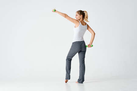 woman goes in for sports with dumbbells in a bright room and gray pants Standard-Bild