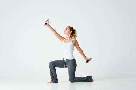 sportive woman with dumbbells in hands doing exercises fitness figure model