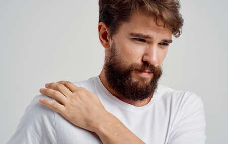 bearded man touching shoulder with hand pain dislocation