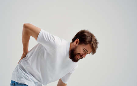 a man touches his back with his hand pain in the spine feeling unwell