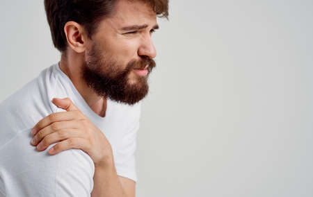 bearded man touching shoulder with hand pain dislocation medical intervention Standard-Bild