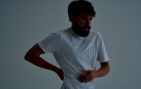 back pain young man in t-shirt beard mustache brunette Standard-Bild