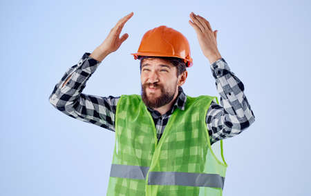 Emotional architect in hard hat and reflective pity gestures with his hands on a blue background