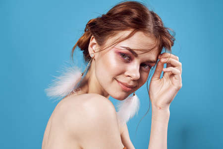 woman with bright makeup on face shoulders luxury blue background