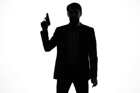 shadow of a man with a gun in his hands aiming detective crime light background