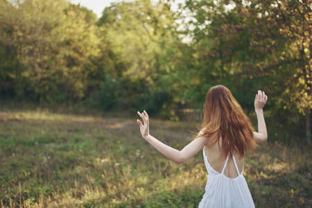 happy women in a sundress runs on green grass in the meadow and trees In the background
