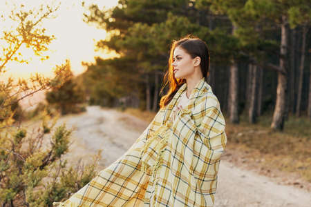 Beautiful woman with a plaid on her shoulders in nature near the bushes and conifers