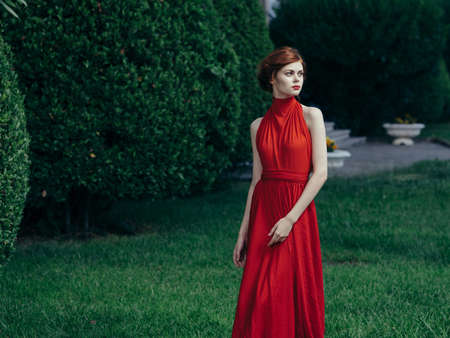 Beautiful woman on luxury attractive look red dress park