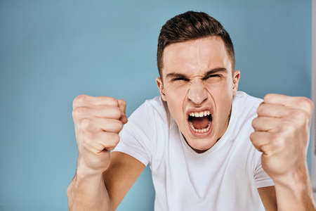 Man gestures with his hands emotions white t-shirt expression blue background