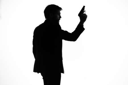 shadow of a man with a gun in his hands aiming suicide danger