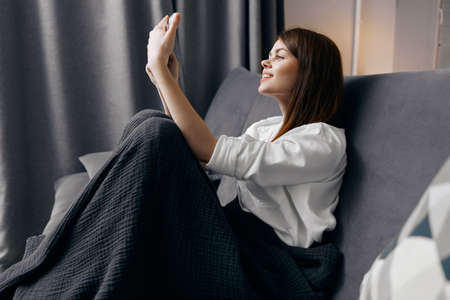 happy woman looking at mobile phone screen and sitting on sofa indoors
