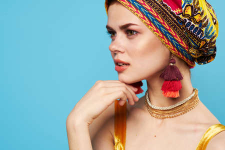 beautiful woman decoration multicolored turban blue background ethnicity Фото со стока