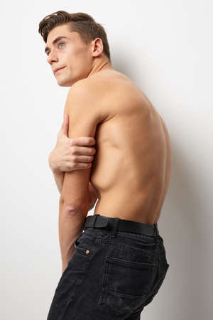 A man with a body stands sideways posing attractive-looking models