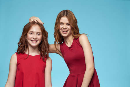 Mom and daughter in red dresses entertainment lifestyle fun studio blue background