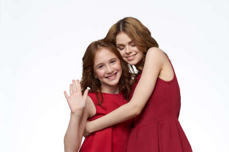 Cheerful mom and daughter next to red dresses hugs lifestyle light background smile Banque d'images