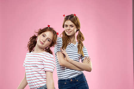 funny girlfriends with clothespins hair on a pink background sisters