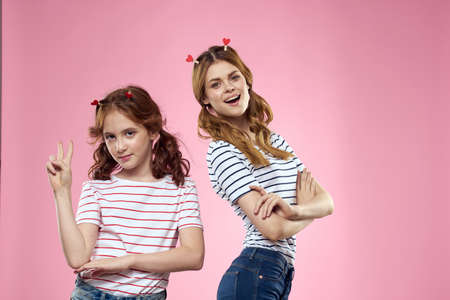 Happy sisters are having fun on a pink background and heart-shaped clothespins on their heads