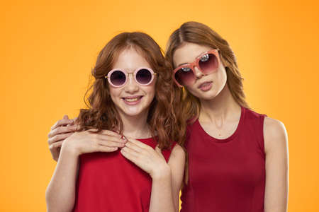 cheerful mom and daughter wearing sunglasses lifestyle friendship family yellow background studio Banque d'images