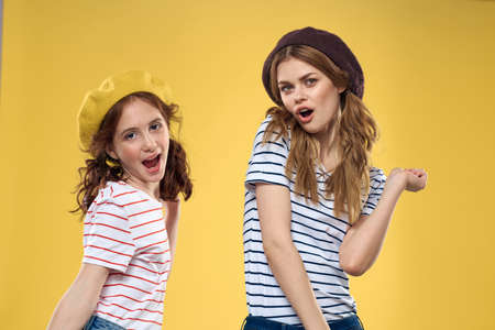 funny mom and daughter wearing hats fashion fun joy family yellow background