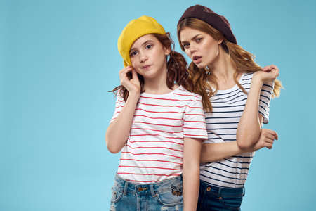 Fashion sisters in hats fun lifestyle blue background studio