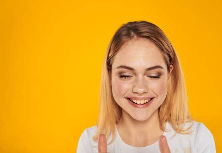 Happy blonde woman laughs on a yellow background in a white t-shirt