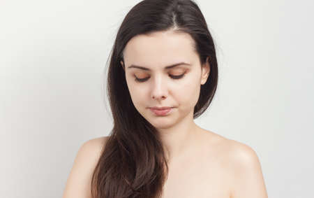 attractive brunette with shoulders holds sponges near her face clean skin